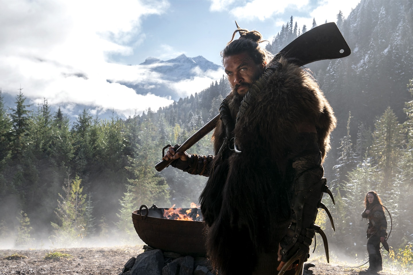A man in the mountains stands with a weapon in front of a fire pit with a woman behind him.