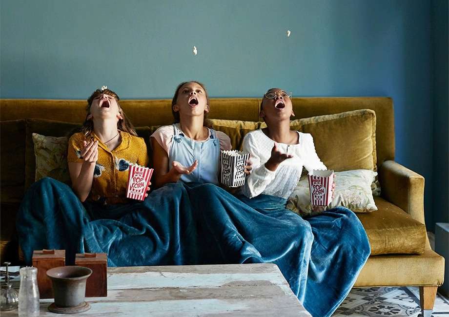 Three friends share a blanket on the couch while throwing popcorn up and catching it in their mouths.
