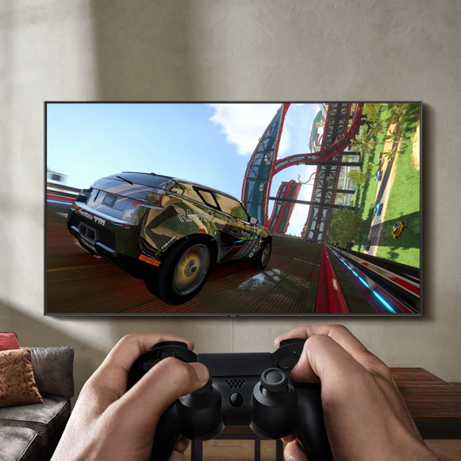 A video game controller shooting controller action symbols at a QLED TV mounted on the wall