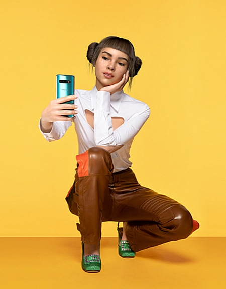 A photo of Lil Miquela against a pale yellow background as she squats down, holding a reflective blue Samsung Galaxy S10 smartphone