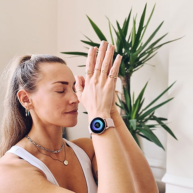 A closeup of Cat Meffan with her palms placed together with her eyes closed. She is wearing a pink Galaxy Watch Active2 with the Breathe feature on-display.