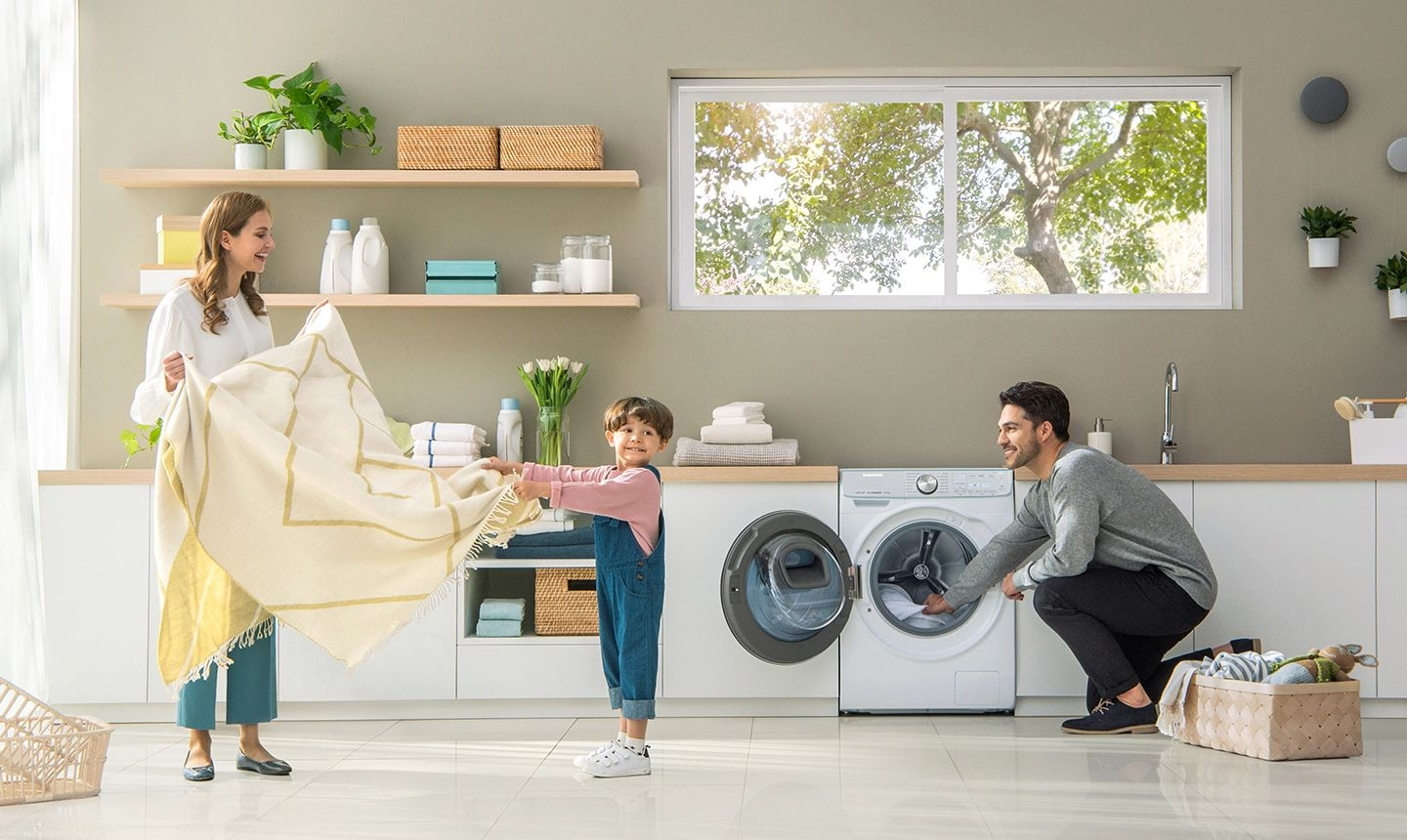 A mother, father and a young son are finishing a load of laundry. The mother and son are joyfully folding a yellow blanket while the father is kneeling by the Samsung QuickDrive™, taking out finished laundry.