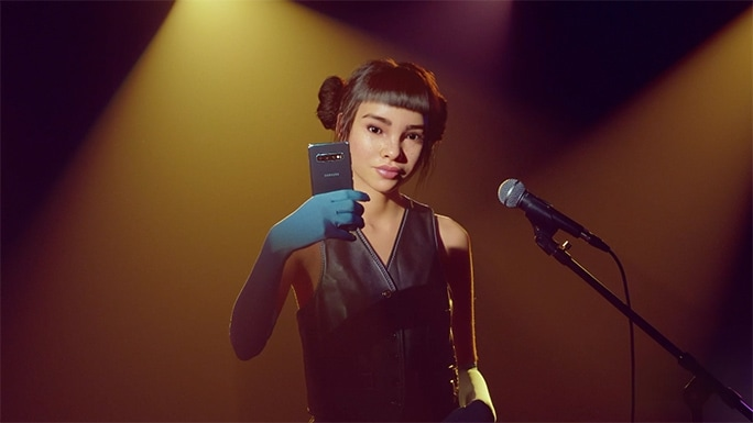 Miquela taking a selfie on a Galaxy S10 as she stands under a spotlight and in front of a microphone