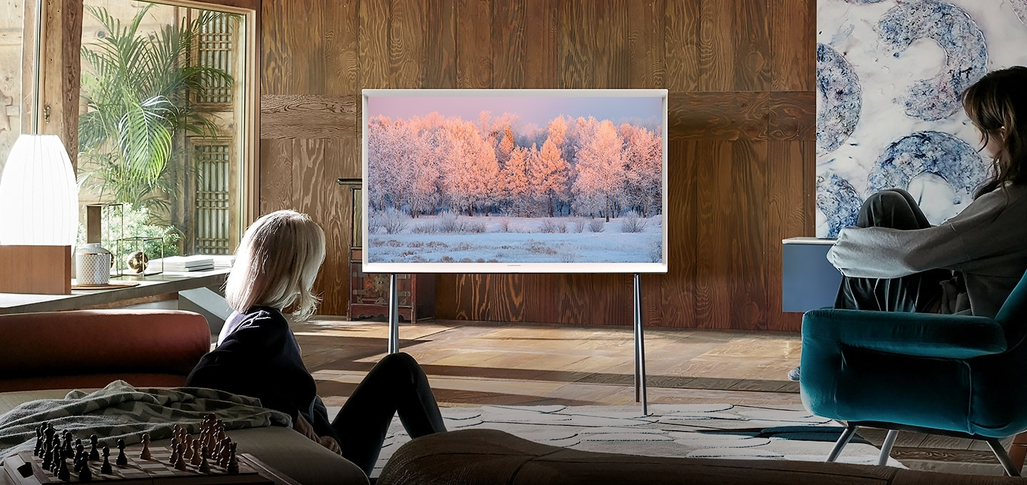 Two women look at a Cloud White model of The Serif TV on a stand in a stylish living room. The image on The Serif's screen shows a winter scene with a forest and snow.