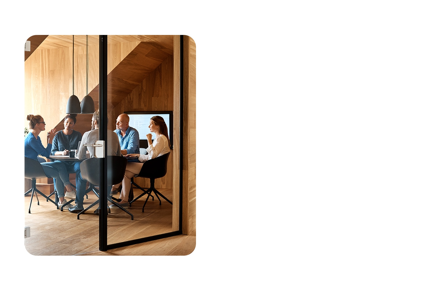 Coworkers meet at a table within a minimalist wooden office space.