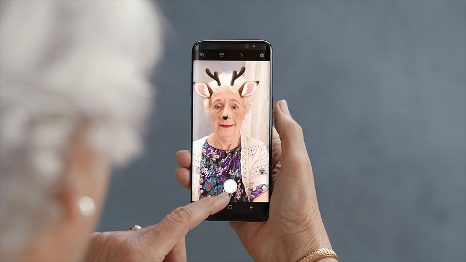 Thumbnail of a person using her Galaxy S8 or S8+ to take a selfie and then decorate it with stickers