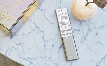 A lifestyle image of one remote put on a marble table.