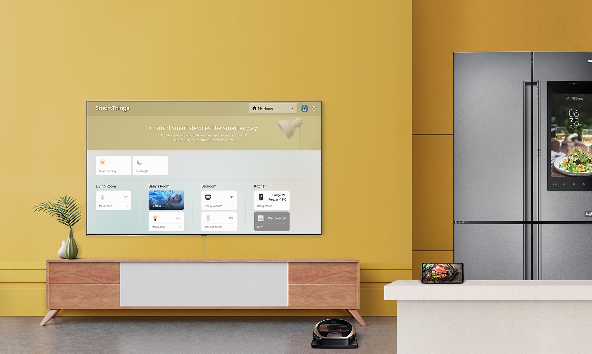 A 2019 Samsung QLED TV displaying a SmartThings dashboard on a smart tv mounted on a wall surrouned by sample connected home appliances and devices: a refridgerator, smart phone, and vacuum cleaner.