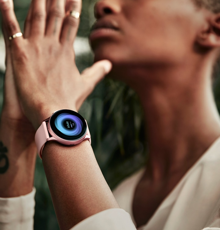 A woman is working out, wearing Galaxy Watch Active2 on her wrist