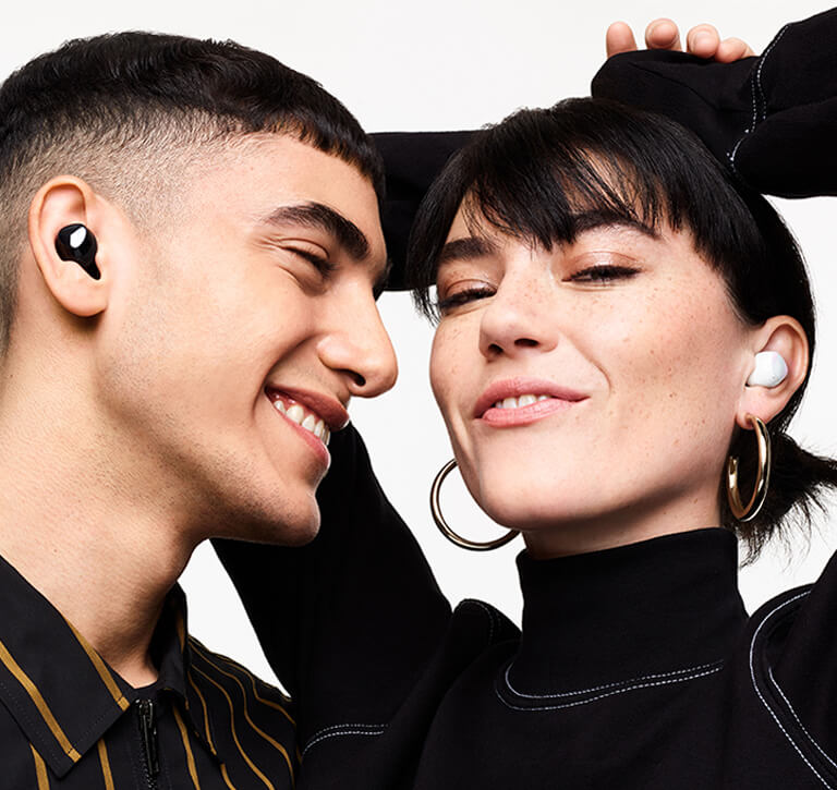 A man wearing black Galaxy Buds plus smiles as he looks a woman next to him wearing white Galaxy Buds plus. The woman smiles with her hands in the air behind her head.