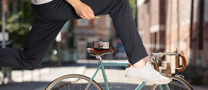A Galaxy Note 9 rests on a seat while the rider is seen in mid air shooting a photo with the S Pen's remote control.