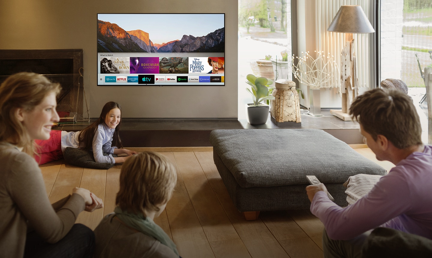 People are watching Smart TV in the living room and Smart Hub UI is displayed over a nature background image on TV screen.