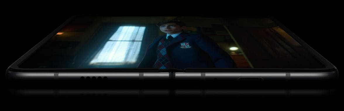 Galaxy Fold unfolded and laying face-up, with two batteries floating over each side of the screen. The display appears on top with a scene from Netflix Original Series The Umbrella Academy on-screen