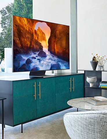 A lifestyle image of the 2019 new Samsung QLED Q90R. A side view of Q90R sitted on the green TV table.