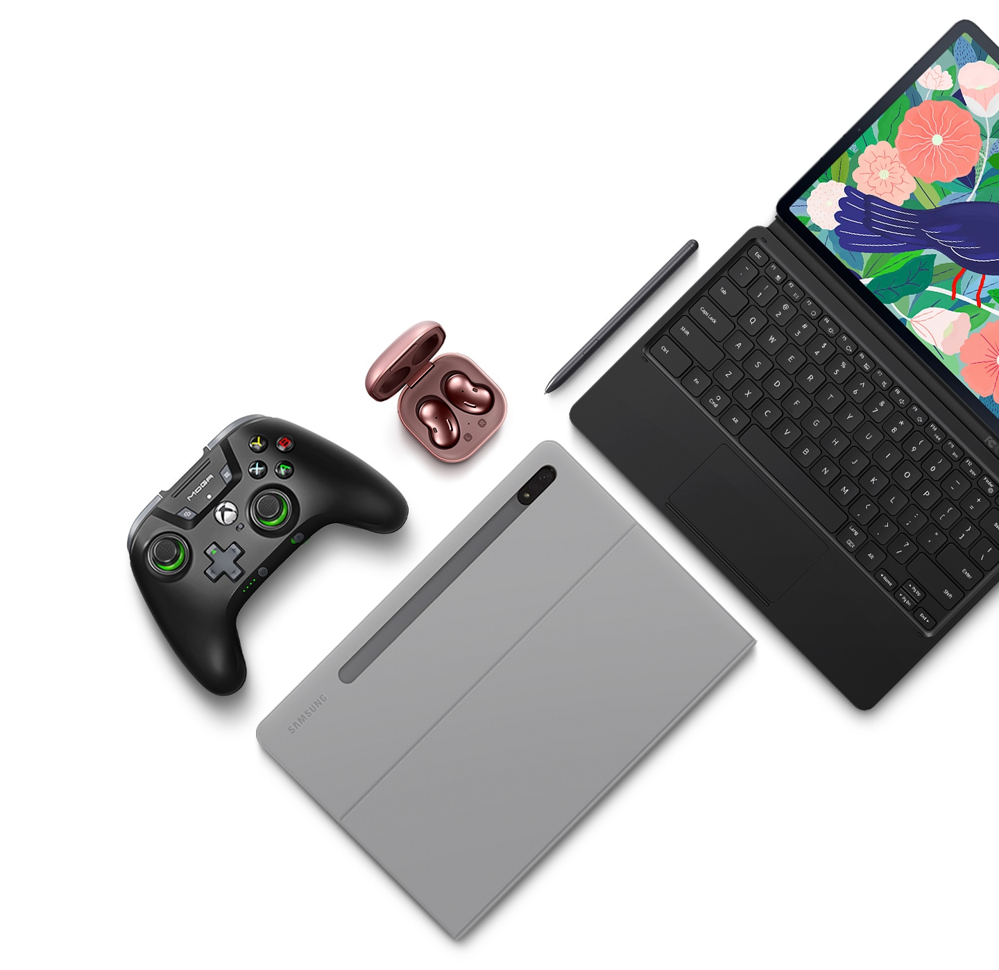Flat lay of Galaxy Tab S7+ and its accessories. A Galaxy Tab S7+ attached to the BookCover Keyboard, a Galaxy Tab S7+ inside the BookCover, S Pen, game controller, and Galaxy Buds Live
