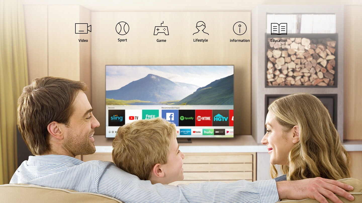 3 people in the living room, are watching Smart TV and various apps are displayed on the TV.