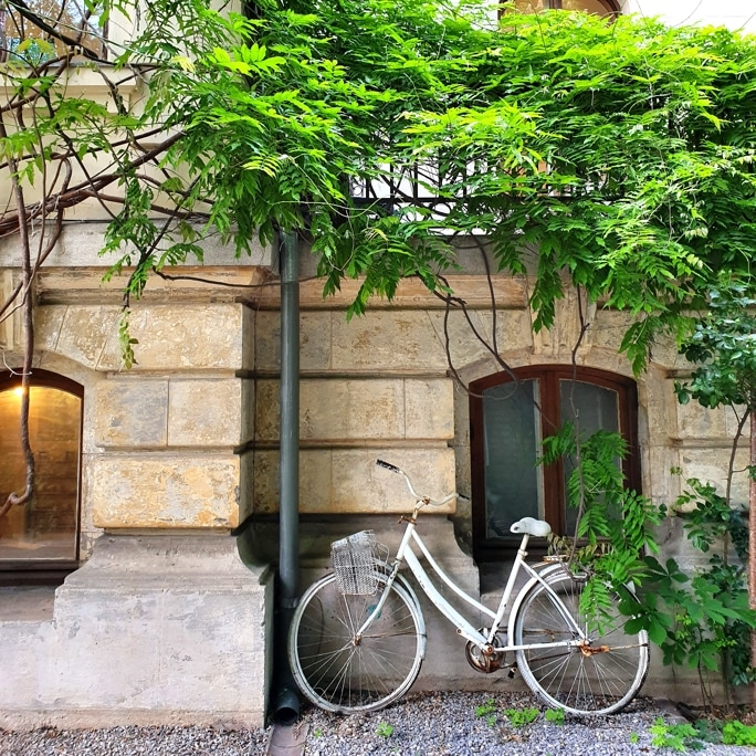 Picture taken with Samsung Galaxy S10 shows white bicycle leaning against a wall with a small window in Arthur Verona Street, Bucharest.