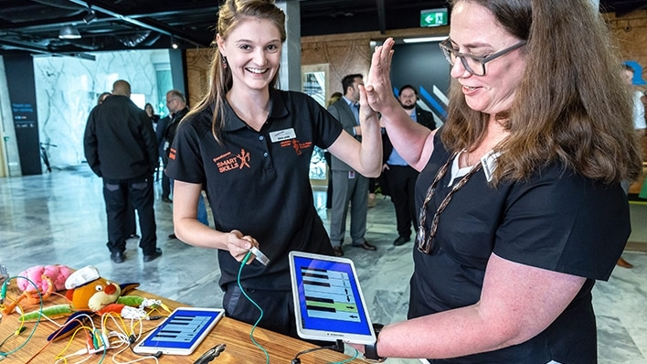 Student holding controller hi-5ing teacher with tablet