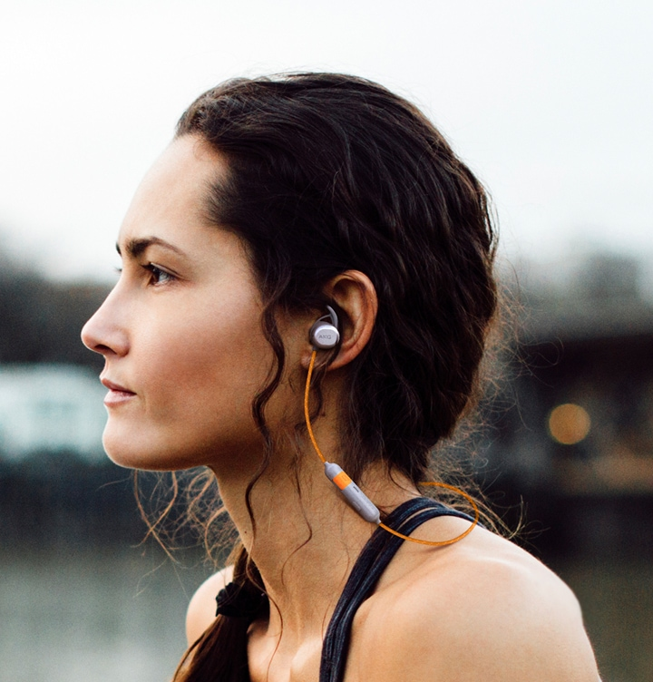 A closeup of a woman in profile wearing AKG N200 Wireless earphones in black
