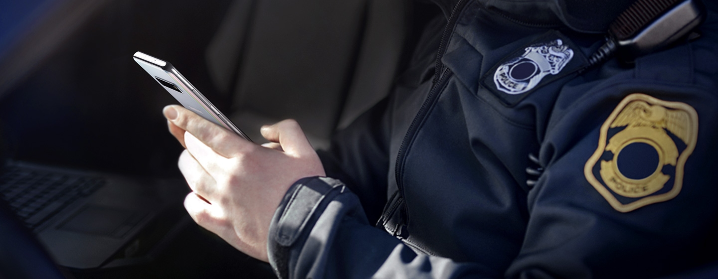 Image of police officer using Galaxy S10 plus while sitting in his car.