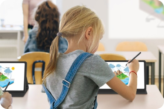 Girl in a classroom drawing on a Galaxy Tab with a weather chart onscreen.