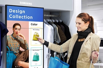 A woman clicking a product image on a Samsung Smart Signage display while shopping