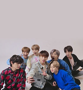 BTS taking Group Selfie. All members are sitting on the ground and taking a BTS selfie on a Galaxy S20+ held by Jung Kook.