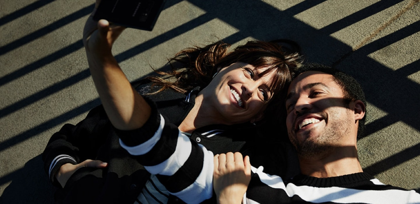 Couple taking selfie for desktop / Grey backgorund for mobile