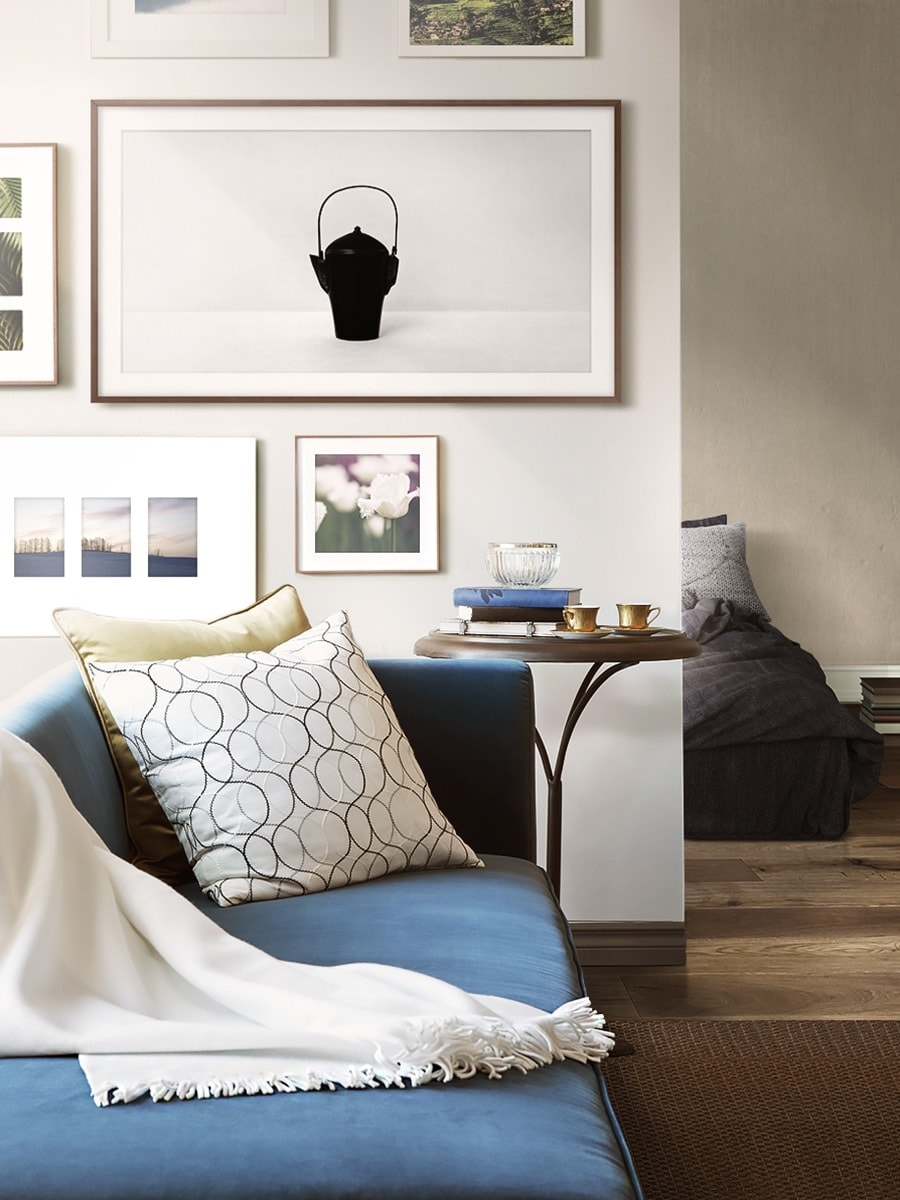 The Frame on the wall with other frames in a living space with a sofa and bed.
