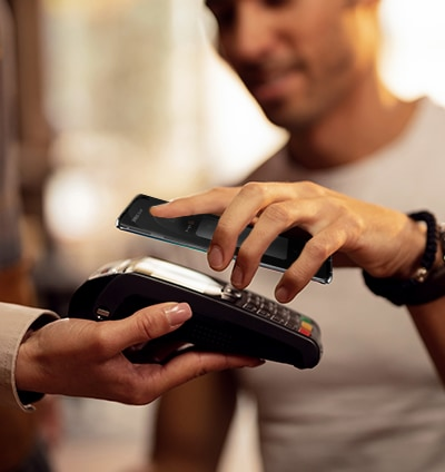 A man is placing his smartphone against the card reader for payment.