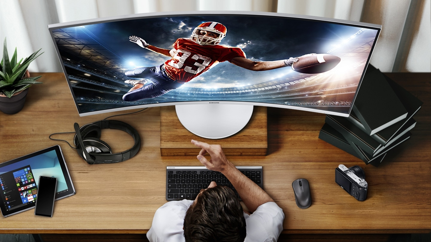 There is a monitor on the room table, and rugby sport is shown on the monitor screen. The man is staring at the monitor, and on the table are tablets, cell phones, headphones, mice, keyboards, cameras, potted plants, and books.