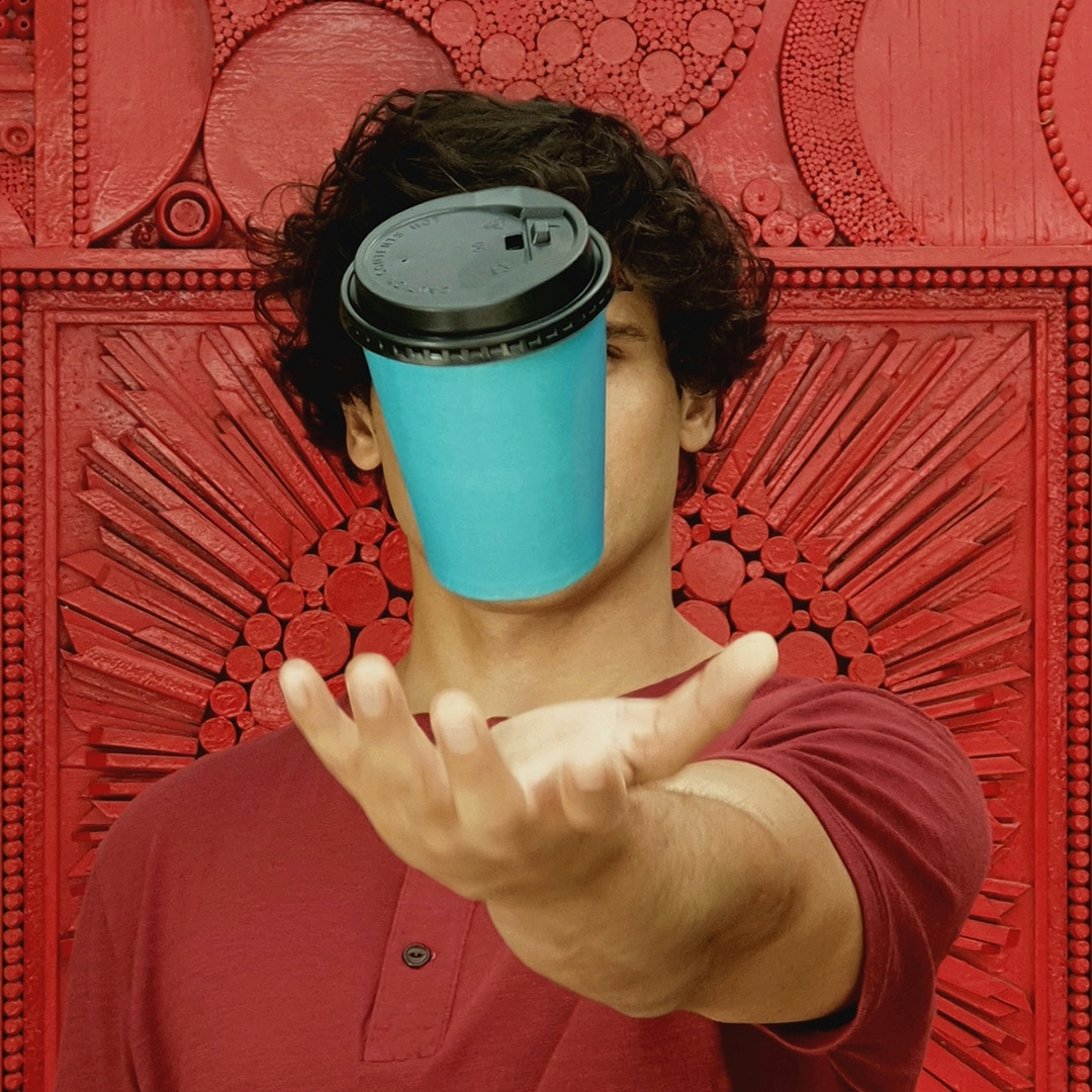 A photo taken by Galaxy Note9 of a man wearing a red shirt, standing against a red wall, throwing a blue paper cup with black lid into the air