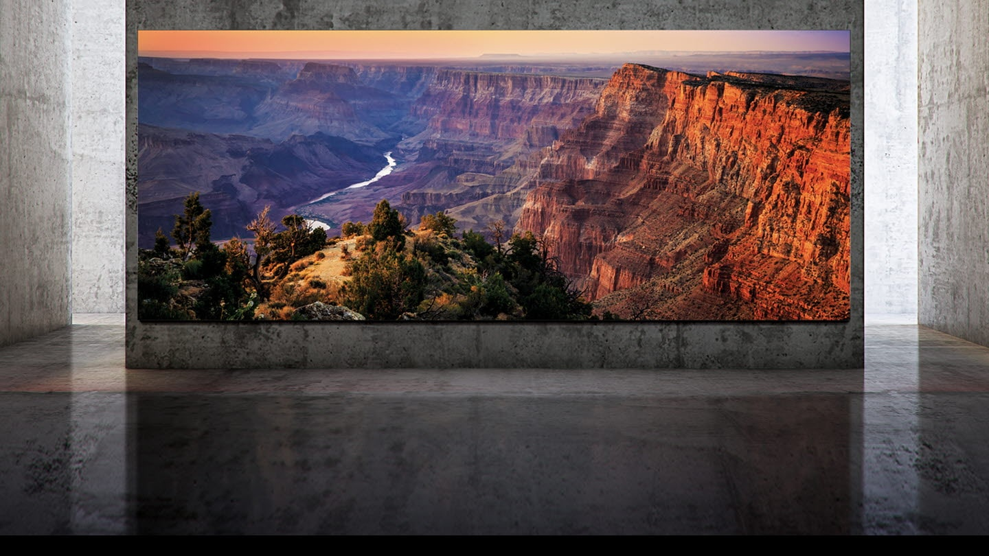 Samsung The Wall mounted on a large concrete wall with a grand view of a cliff at sunset