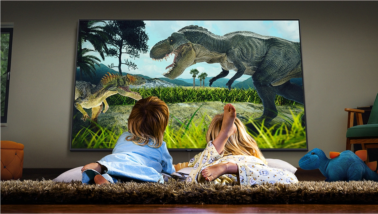 Two children wearing pajamas and laying on the floor are watching a realistic dinosaur movie on a big screen TV.