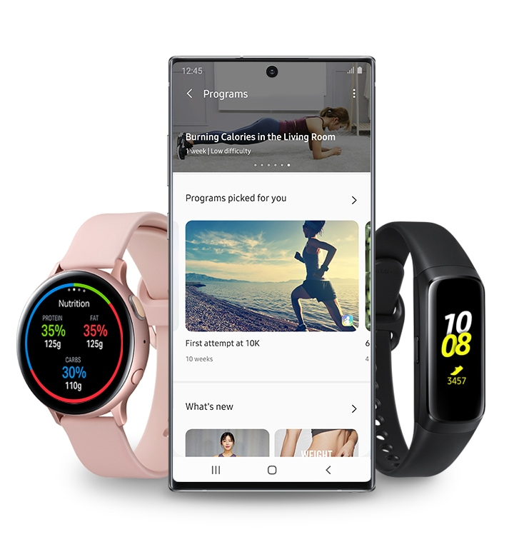 Galaxy Watch Active2 in pink gold and Galaxy Fit in black on either size of a Galaxy smartphone with the Fitness Programs section of the Samsung Health app onscreen