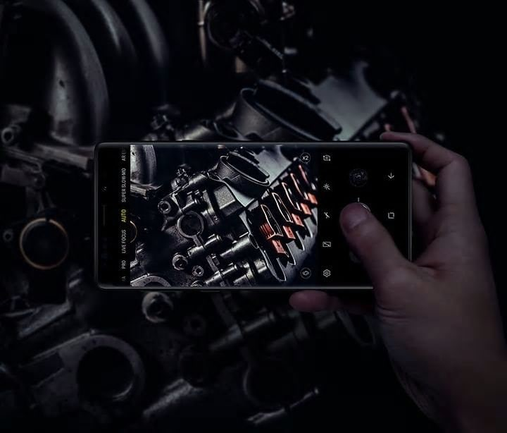 Image of person holding Galaxy Note9 and taking a photo of equipment in low light, demonstrating Dual Aperture