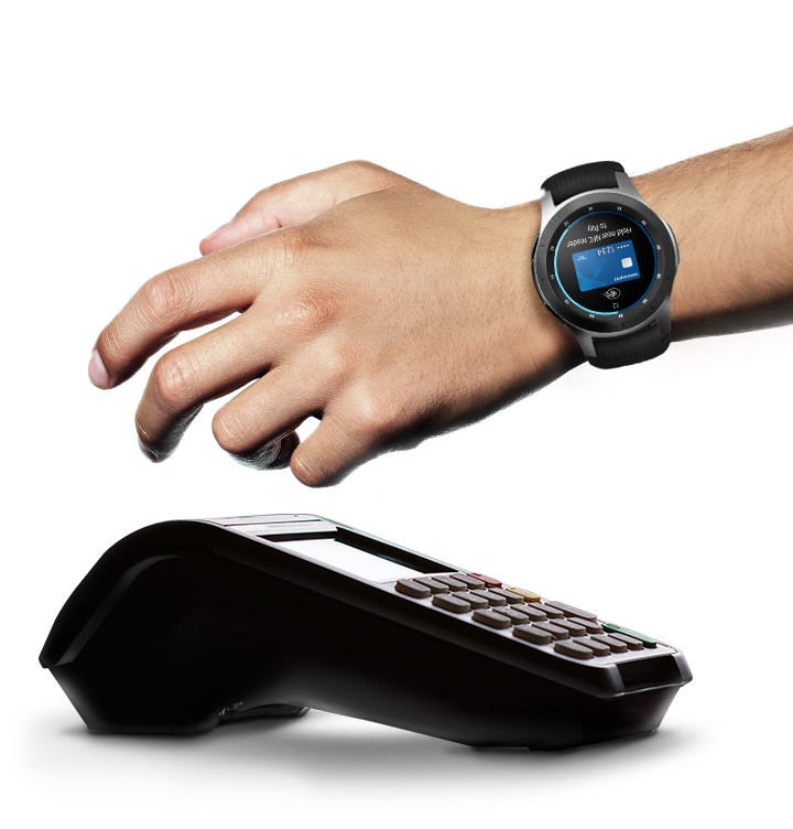 Galaxy watch worn on the left wrist with hand held over top of POS terminal. Watch face is front-facing with screen showing Samsung Pay App completing the transaction.