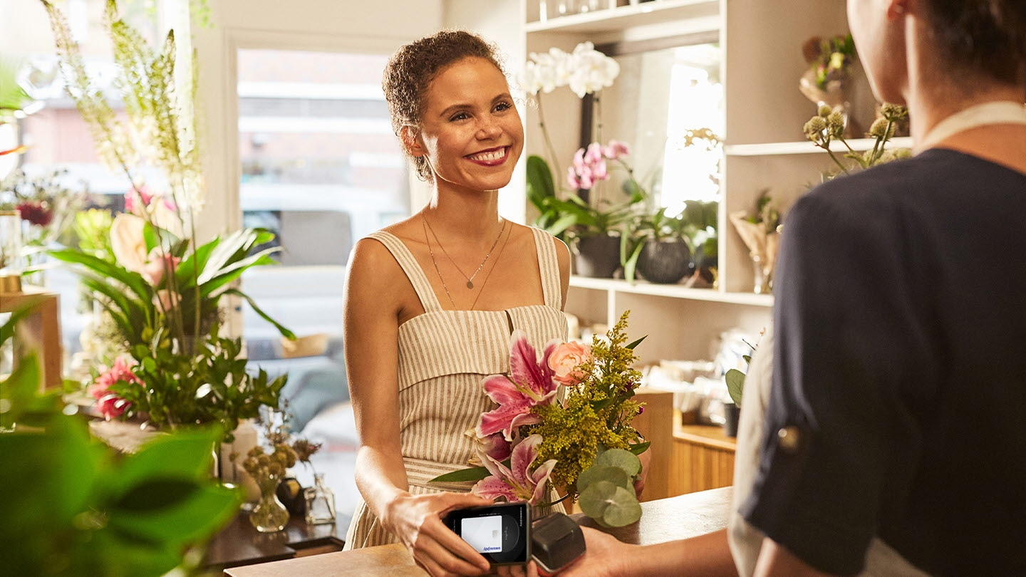 image of women in a flower shop facing the cashier holding a galaxy smartphone over the merchant POS terminal using Samsung Pay to complete the transaction.