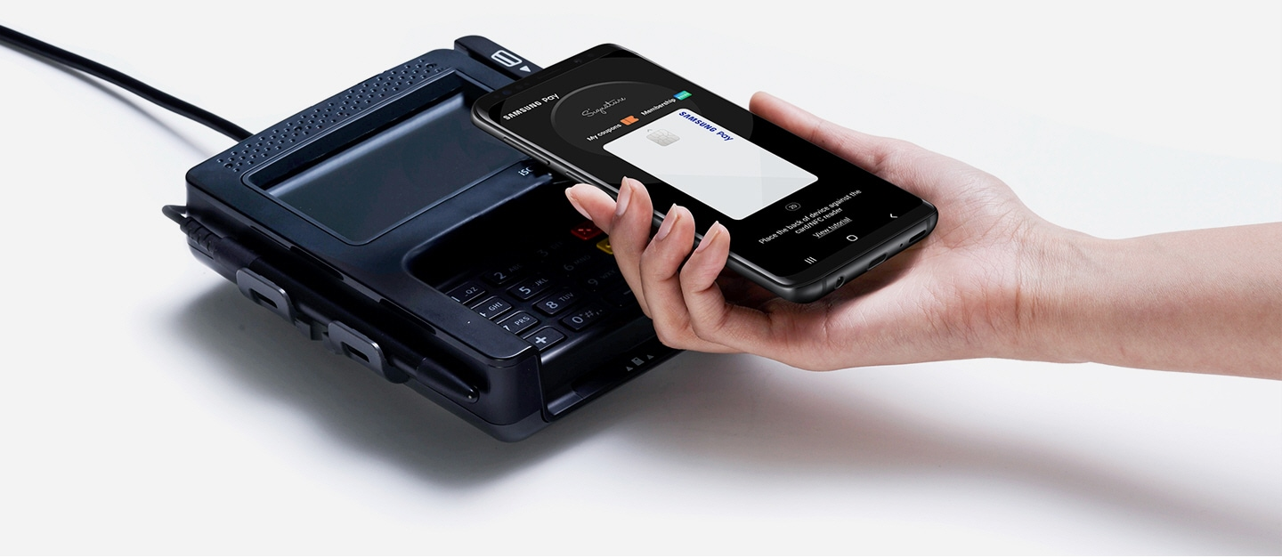 image of right hand holding a galaxy smartphone face up over a POS terminal with screen showing Samsung Pay app in-use.