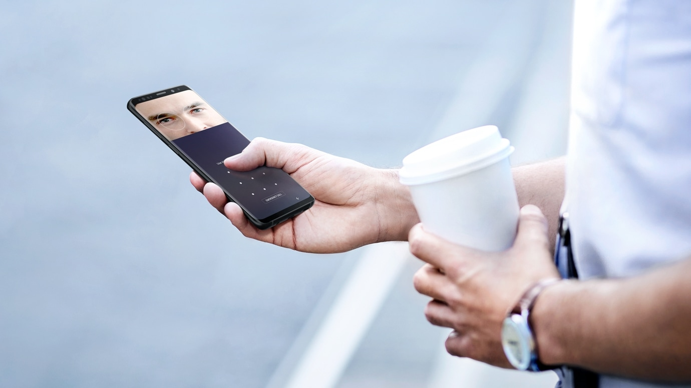 Image of person outside holding a cup of coffee in one hand and Galaxy S9 or S9+ in the other displaying Intelligent Scan GUI