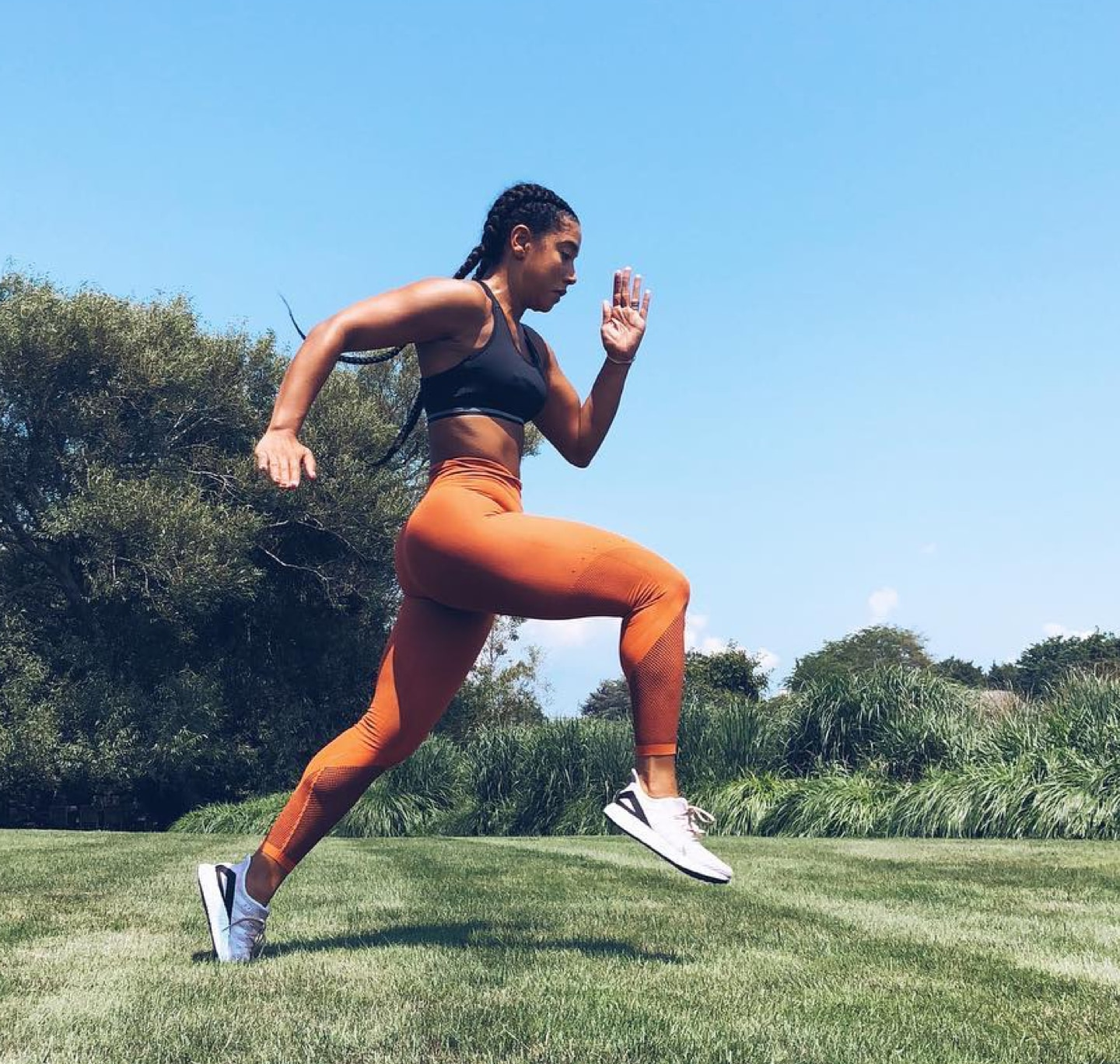 A full-body side shot of Hannah Bronfman mid-run in a park
