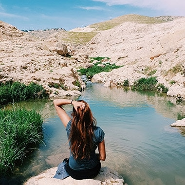 A photo captured with Galaxy by Instagram user @shovali123 of a girl sitting on a rock in front of a small waterway and rocky hills