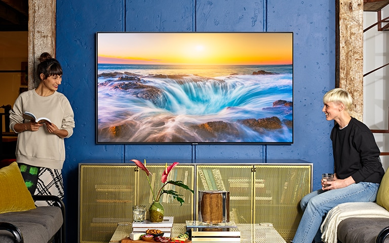 A lifestyle image of the 2019 new Samsung QLED Q85R. Image shows Q85R mounted on the blue wall with clean look. And two young people are talking the each other in front of TV.