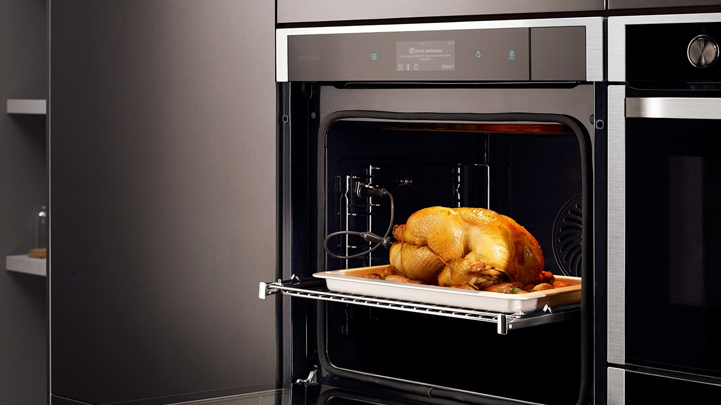 A whole roast chicken is on a upper rack of a Samsung oven.