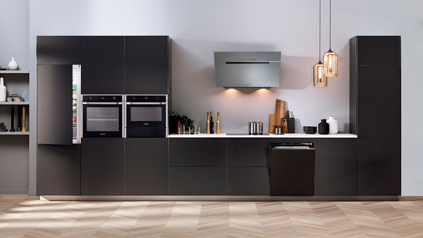 A full package of Samsung Built-in appliances, such as refrigerator, oven, compact oven, cooktop, dishwasher and hood, is installed in a premium dark grey kitchen, while the doors of refrigerator and dishwasher are slightly opened.
