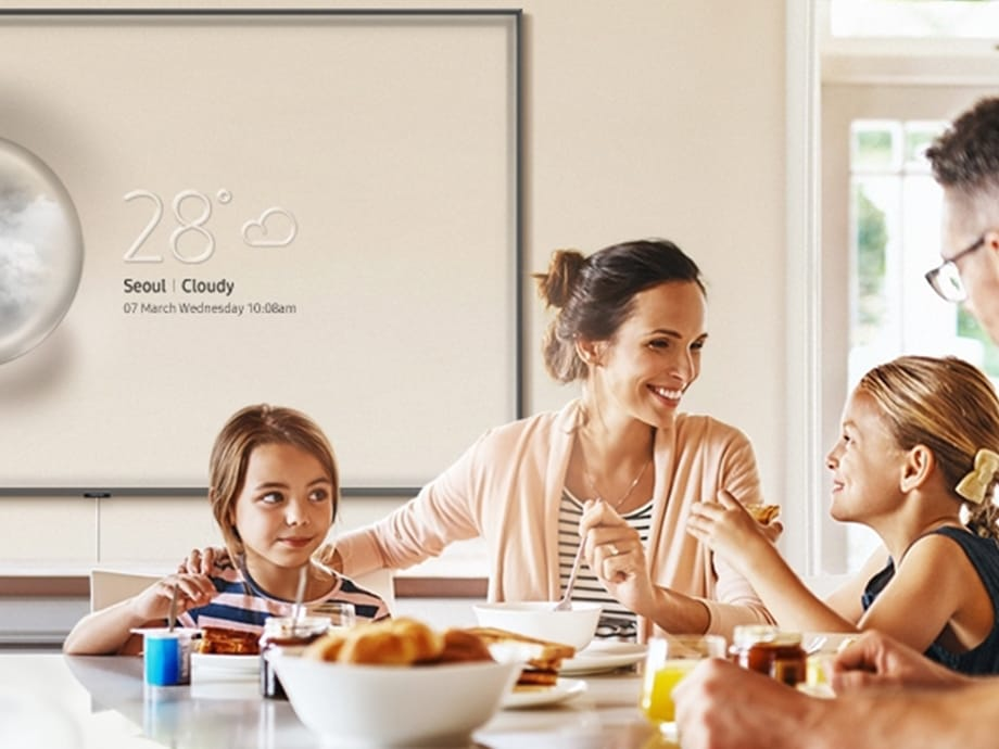 A family is sitting on a dining table and having a meal together. Behind them, QLED TV is hung on the wall with its Info mode on. With its Info display mode, QLED TV with Ambient Mode turns into weather information board in the kitchen.