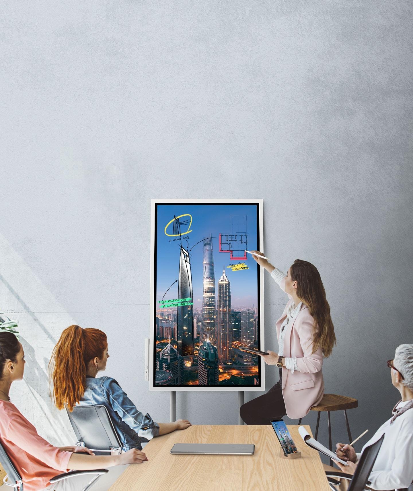 Una imagen que muestra a cuatro personas en una reunión donde se conectan un dispositivo Samsung Flip y un teléfono inteligente, mostrando las mismas imágenes. Miran la pantalla del Samsung Flip posicionado en modo Portait y dos de ellos toman notas.