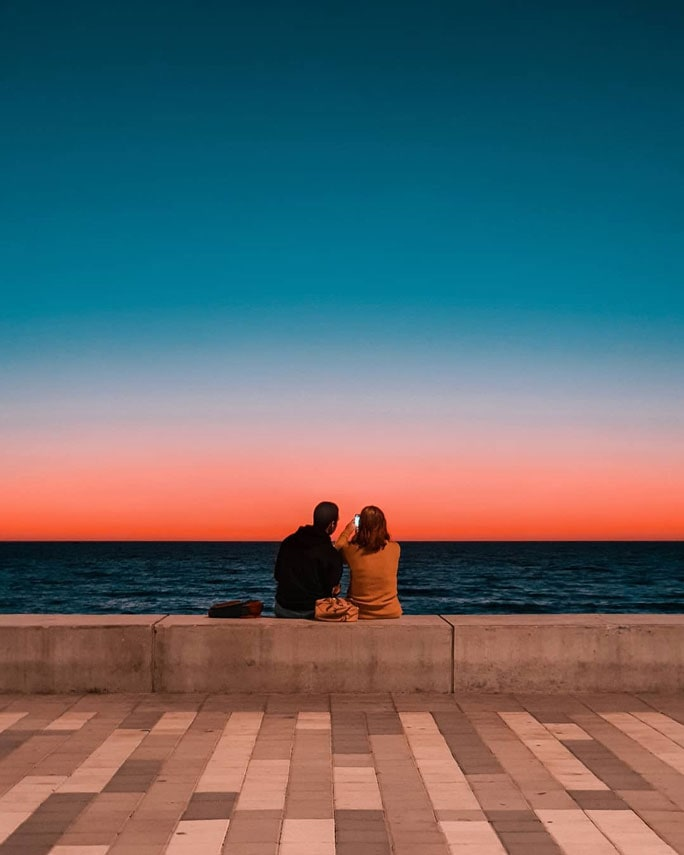 A couple sitting on a concrete wall looking out on the ocean, there is  a striking sunset that creates a colourful gradient in the sky.