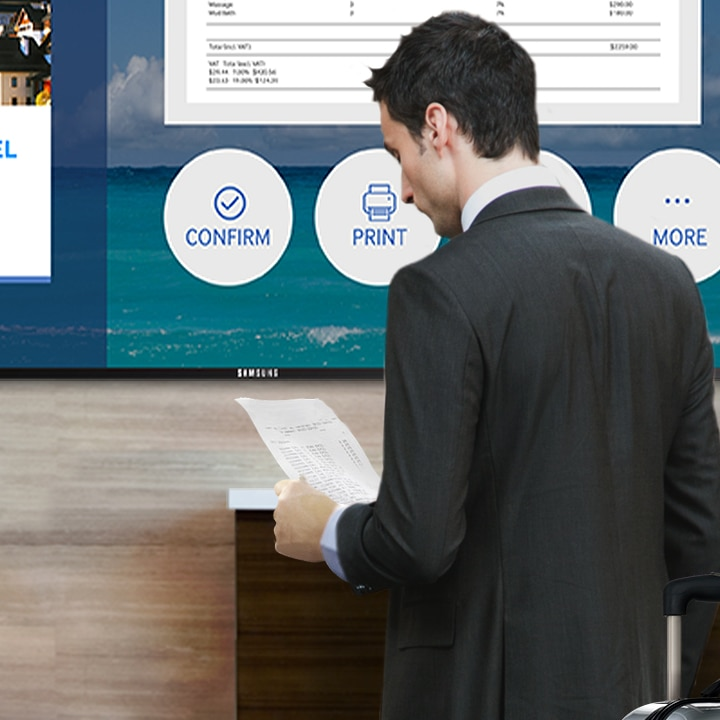A businessman with a suitcase checking in at a hotel using Samsung SMART Signage TV