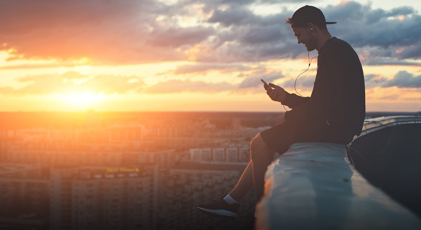 Young man sitting on a high ledge above city smiling and looking at his phone